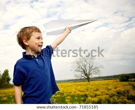 Boy Flying a Paper Airplane - stock photo