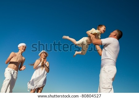 Boy flying on his father's hands at beach - stock photo