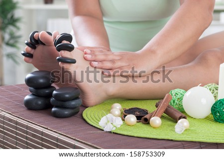 boy foot ready to spa treatment with massage stones - stock photo