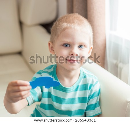 boy four years cut from a sheet of blue cardboard machine, smiling and showing applique
