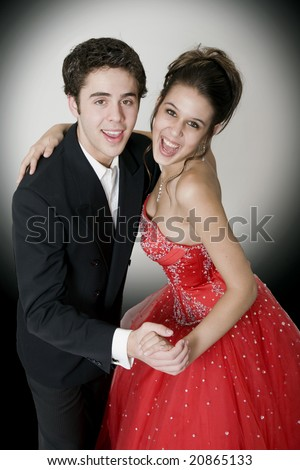 Boy & girl, in formal attire, dancing at their high school prom. - stock photo