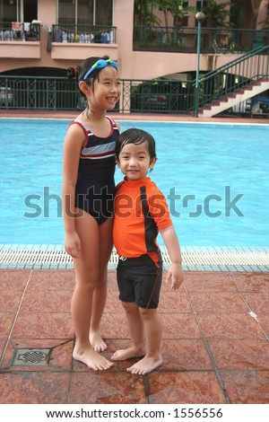 boy & girl with swimming costume at the pool - stock photo