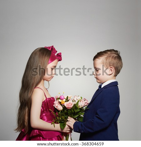 boy gives a girl flowers.little beautiful couple.kids love,valentine.roses bouquet