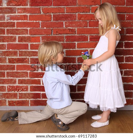 Boy gives a girl flowers. Love concept - stock photo