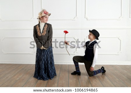 Boy gives flower to girl - young gentleman and lady in vintage clothes and hats, an offer a marriage, romance
