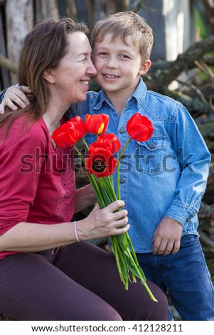 Boy gives red flowers tulips his grandmother on a holiday - stock photo