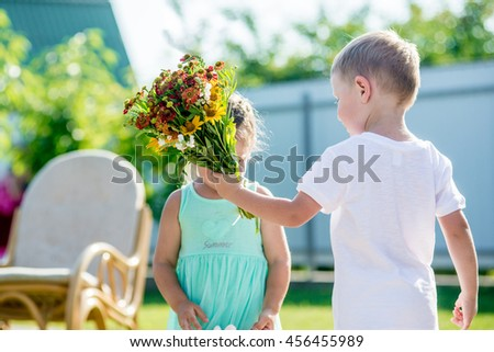 boy giving bouquet of spring flowers to happy girl