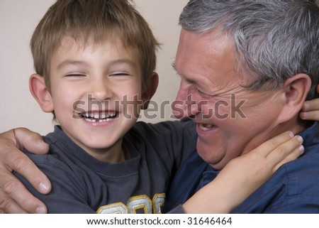 Boy giving his grandfather a huge hug - stock photo