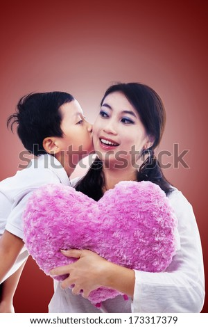 Boy giving his mother a Valentine's day kiss. The mother is holding a heart-shaped pillow. Red background. - stock photo