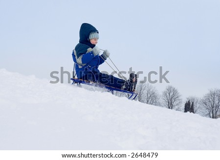 boy goes from hill at winter on sleigh