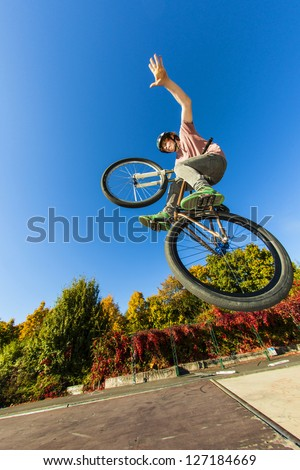 boy going airborne with his dirt bike and showing a non hander - stock photo