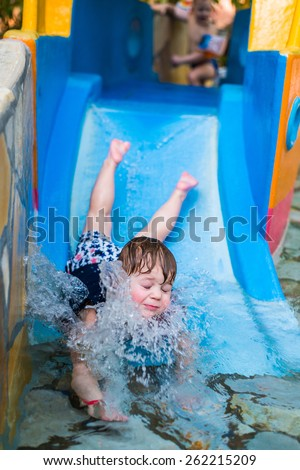 boy going from the water slide splash in color - stock photo