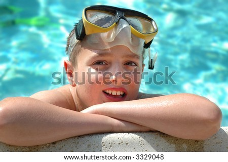 Boy grinning while posing in the pool - stock photo