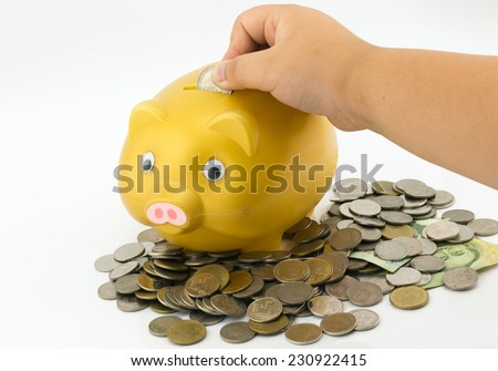 boy hand inserting a coin into a piggy bank - stock photo