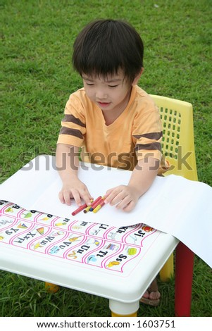 Boy happily coloring with crayon - stock photo