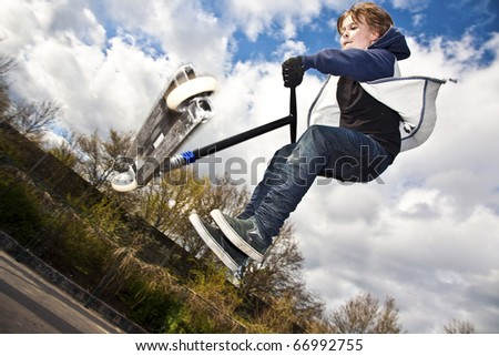 boy has fun by riding his scooter