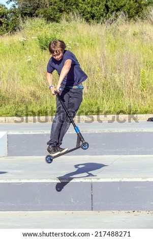 boy has fun riding his push scooter at the skatepark - stock photo