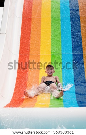 Boy has into pool after going down water slide during summer  - stock photo