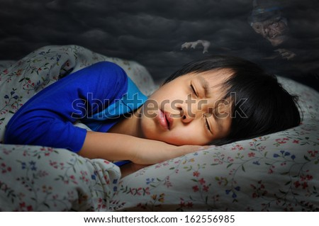 Boy having a scary dream (witch in dark clouds hanging above the boy) - stock photo