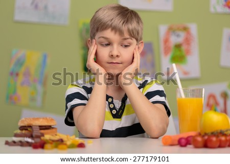 Boy having choice - healthy or unhealthy lunch - stock photo