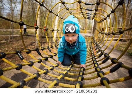 Boy having fun in playground on ropes