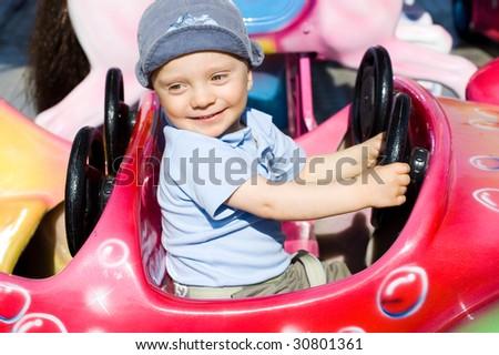 Boy having fun on carrousel - stock photo