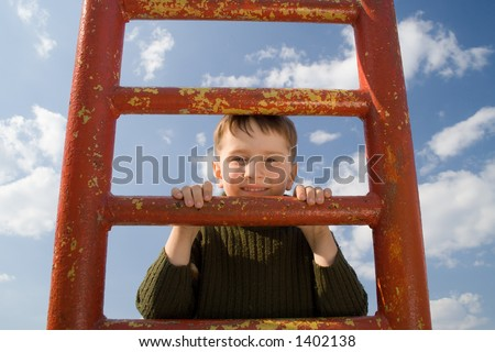 Boy having fun on the ladder - stock photo