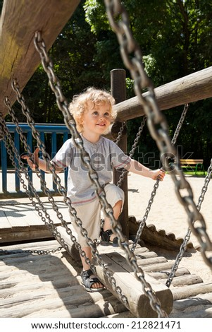 Boy having fun on the playground during sunny day - stock photo