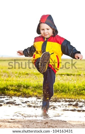 Boy having fun, splashing in puddle - stock photo