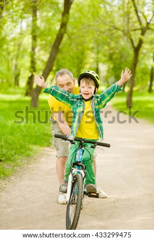 Boy having fun with his grandfather on a bicycle. - stock photo