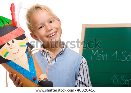 Boy having his first schoolday standing beside chalkboard