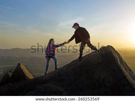 Boy helping hand girl on sunset sky background. Wichita Mountains National Wildlife Refuge  - stock photo