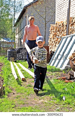 boy helps to carry log