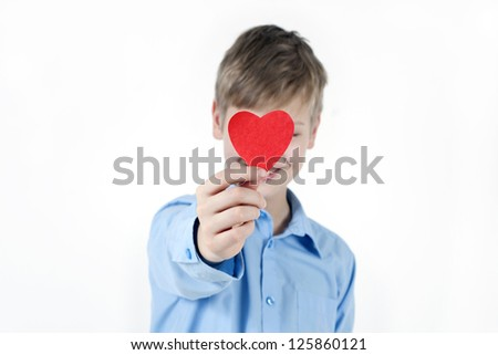 Boy hiding himself behind a red heart.Valentines Day concept. - stock photo