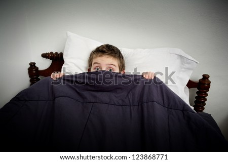 Boy hiding in bed under the covers - stock photo