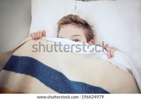 Boy hiding under the covers, peeking out - stock photo