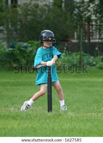 Boy hitting ball off of the Tee - stock photo