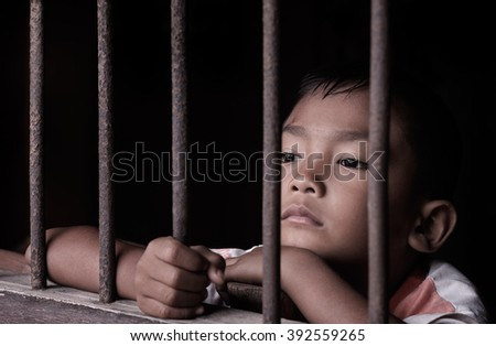 Boy hold cage with eye sad and hopeless - stock photo