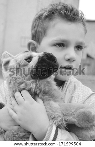 Boy holding a favorite stuffed toy dog shepherd..black and white photo.