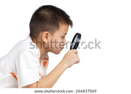 Boy holding a magnifying glass - stock photo