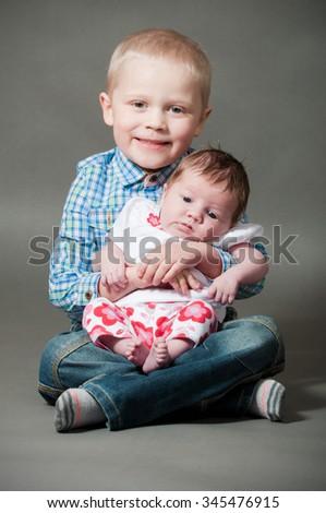 Boy holding a new born baby - stock photo