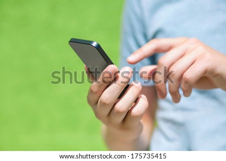 boy holding a phone and a touch screen for finger against a green wall - stock photo