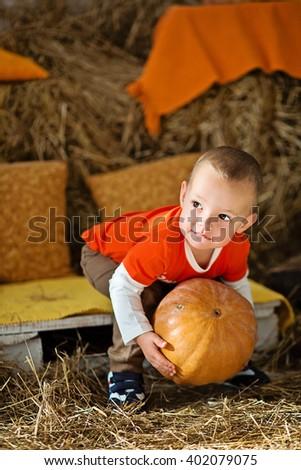 Boy holding a pumpkin. Autumn decor. Halloween - stock photo