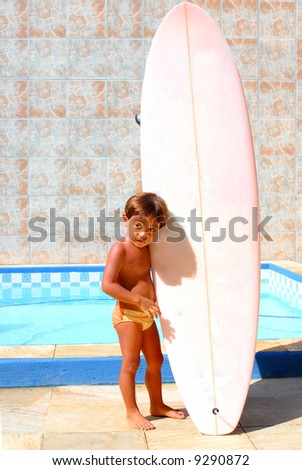 Boy holding a Surf board on the swimming pool.