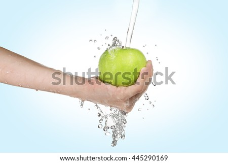 boy holding and washing a green apple  - stock photo