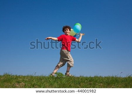 Boy holding balloons, playing outdoor