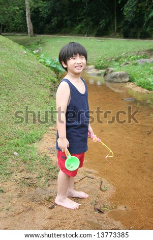 Boy holding fishing rod standing by the river - stock photo