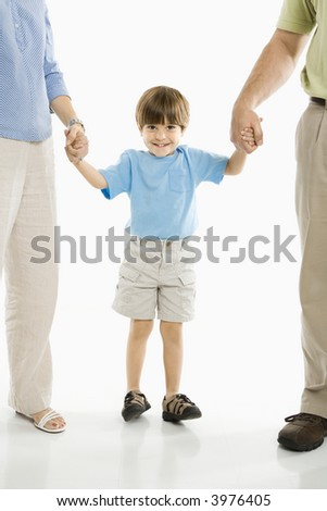 Boy holding hands with parents standing against white background. - stock photo