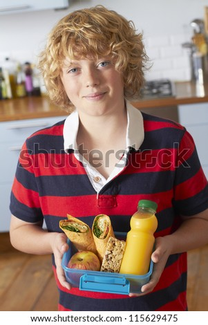 Boy Holding Healthy Lunchbox In Kitchen - stock photo