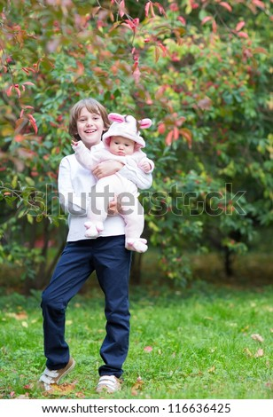 Boy holding his baby sister standing under a red autumn tree - stock photo